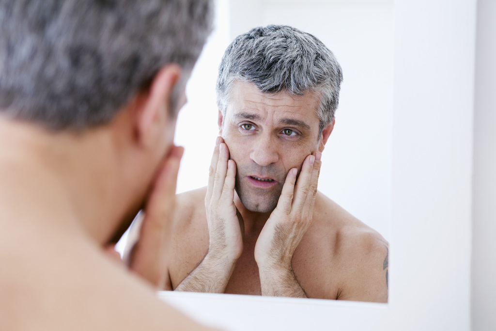aging man looking in mirror