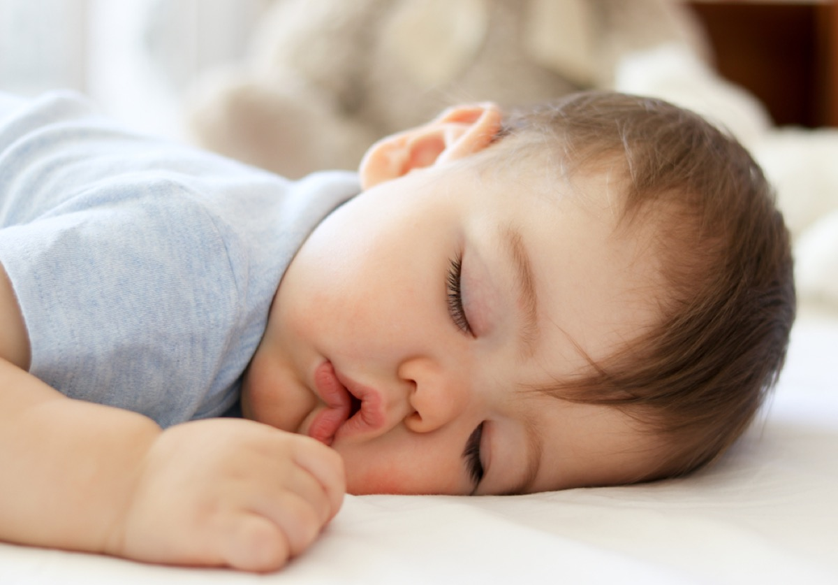 white baby with brown hair sleeping on her stomach