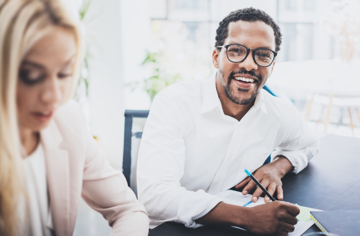 man at work smiling in thick eyeglasses, make yourself more attractive