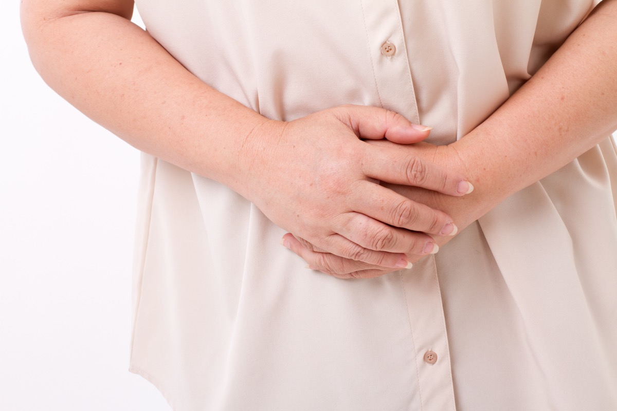 older woman in pain, holding her stomach, subtle symptoms of serious disease