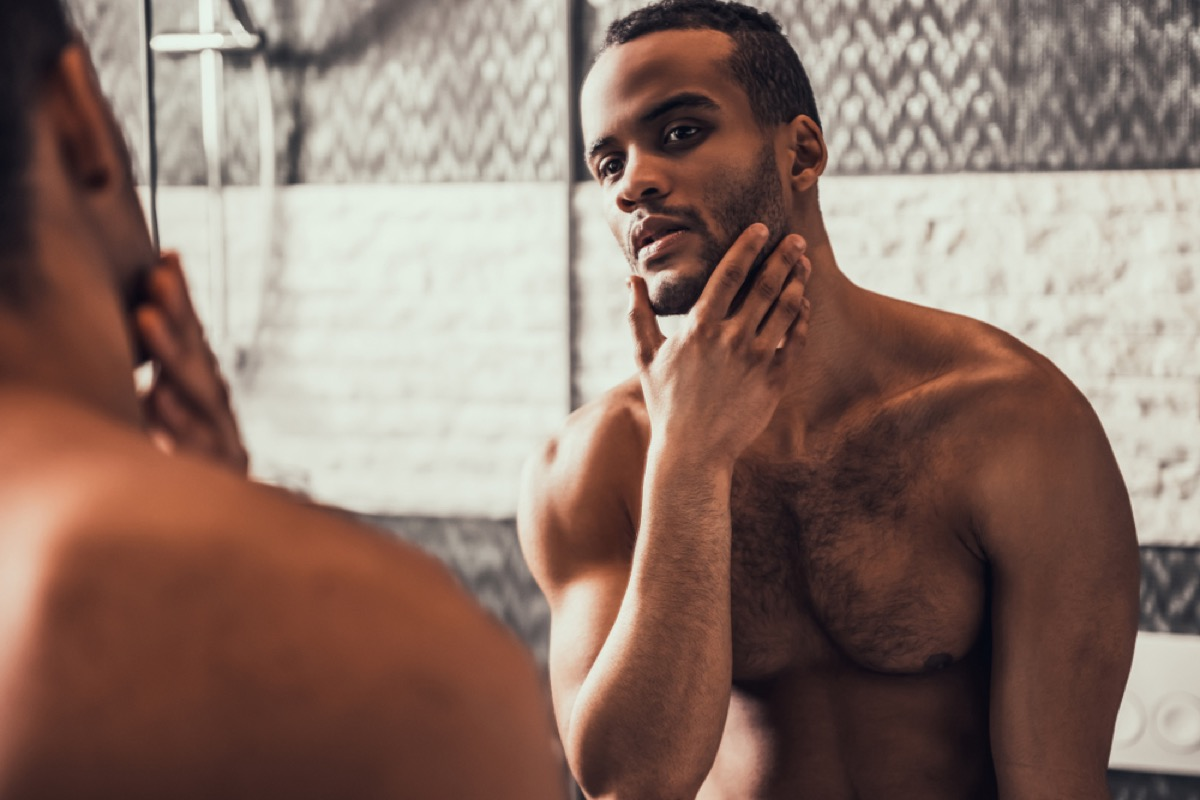 young shirtless man looking in mirror, moisturizing which helps fend off aging
