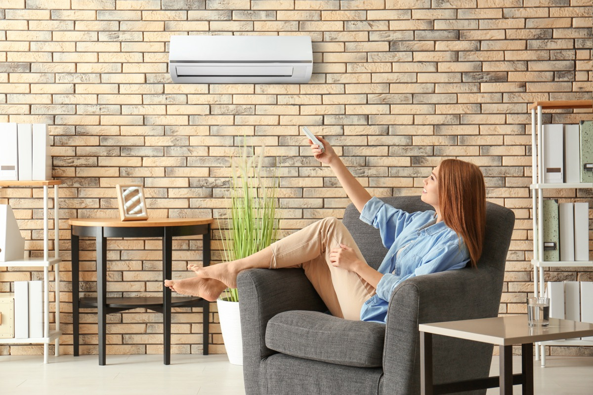 woman adjusting air conditioner, bad home renovations