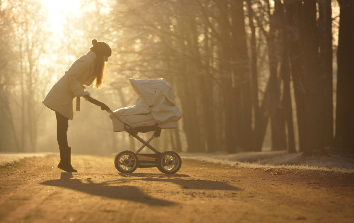 woman looking in stroller bassinet, ways parenting has changed.