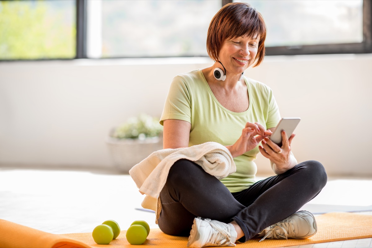 woman on phone at the gym, over 40 fitness