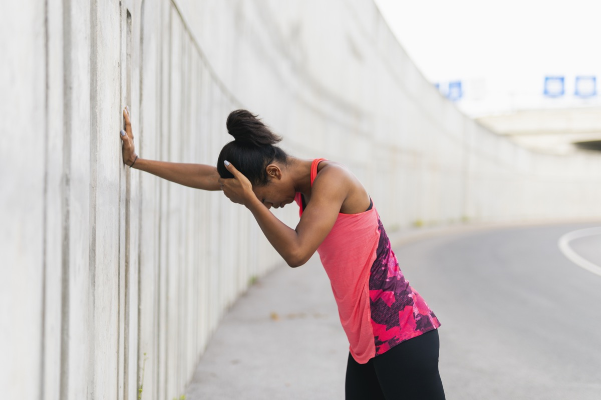 Woman feeling sick and dizzy while going for an outdoor run or jog