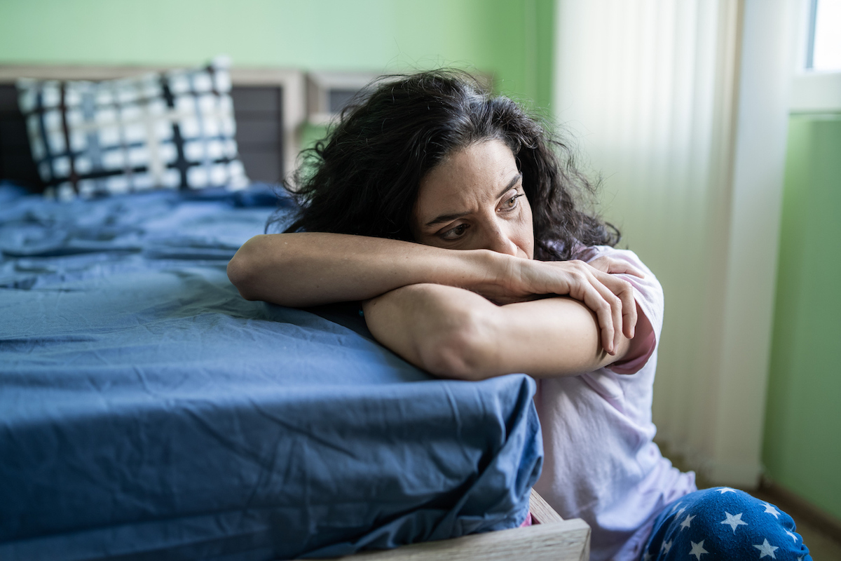 Mid adult woman sitting home alone, worried