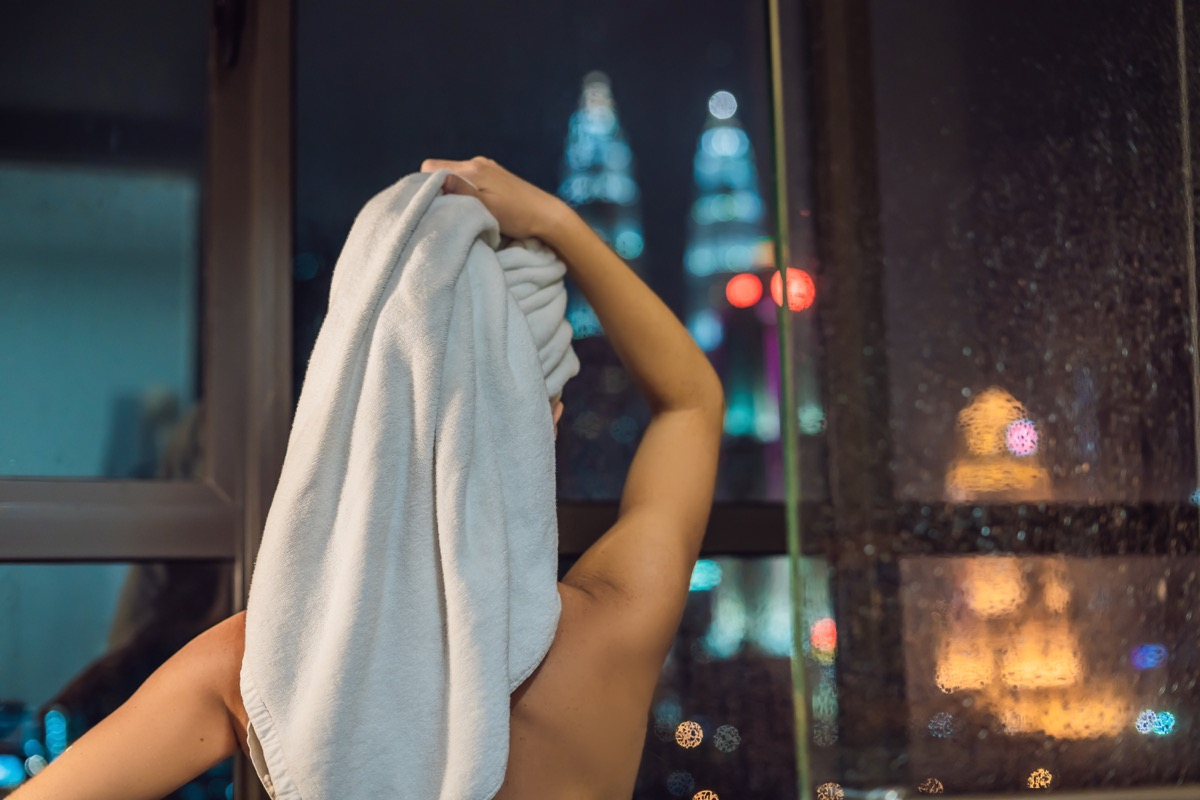 woman showering at night ways to bring down a/c bill