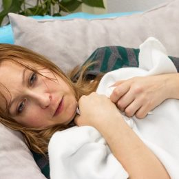 Woman sick in bed with night sweats