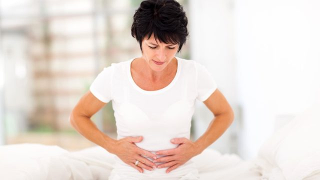 Woman clutching her stomach in pain