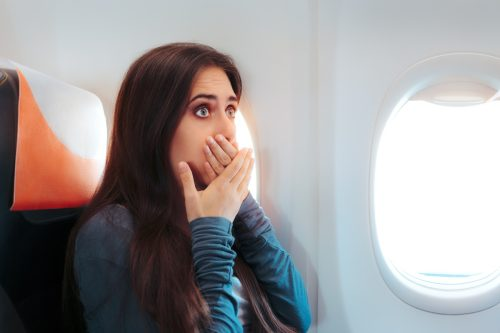 woman with motion sickness on airplane