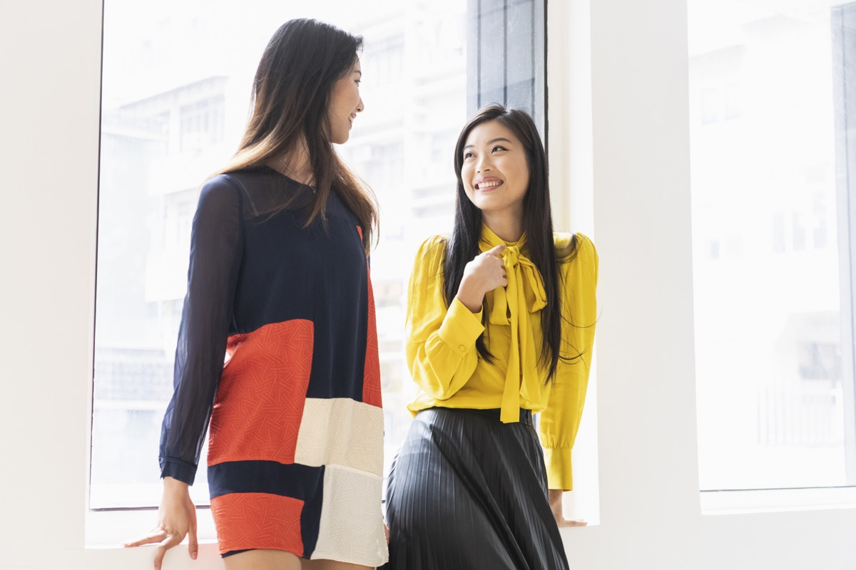 Mid adult woman talking to friend, smartly dressed, fashionable clothes, stylish, modern clothing