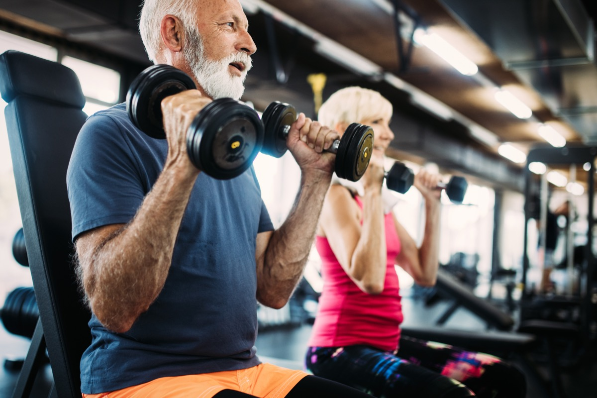 Older couple lifting weights working out at the gym