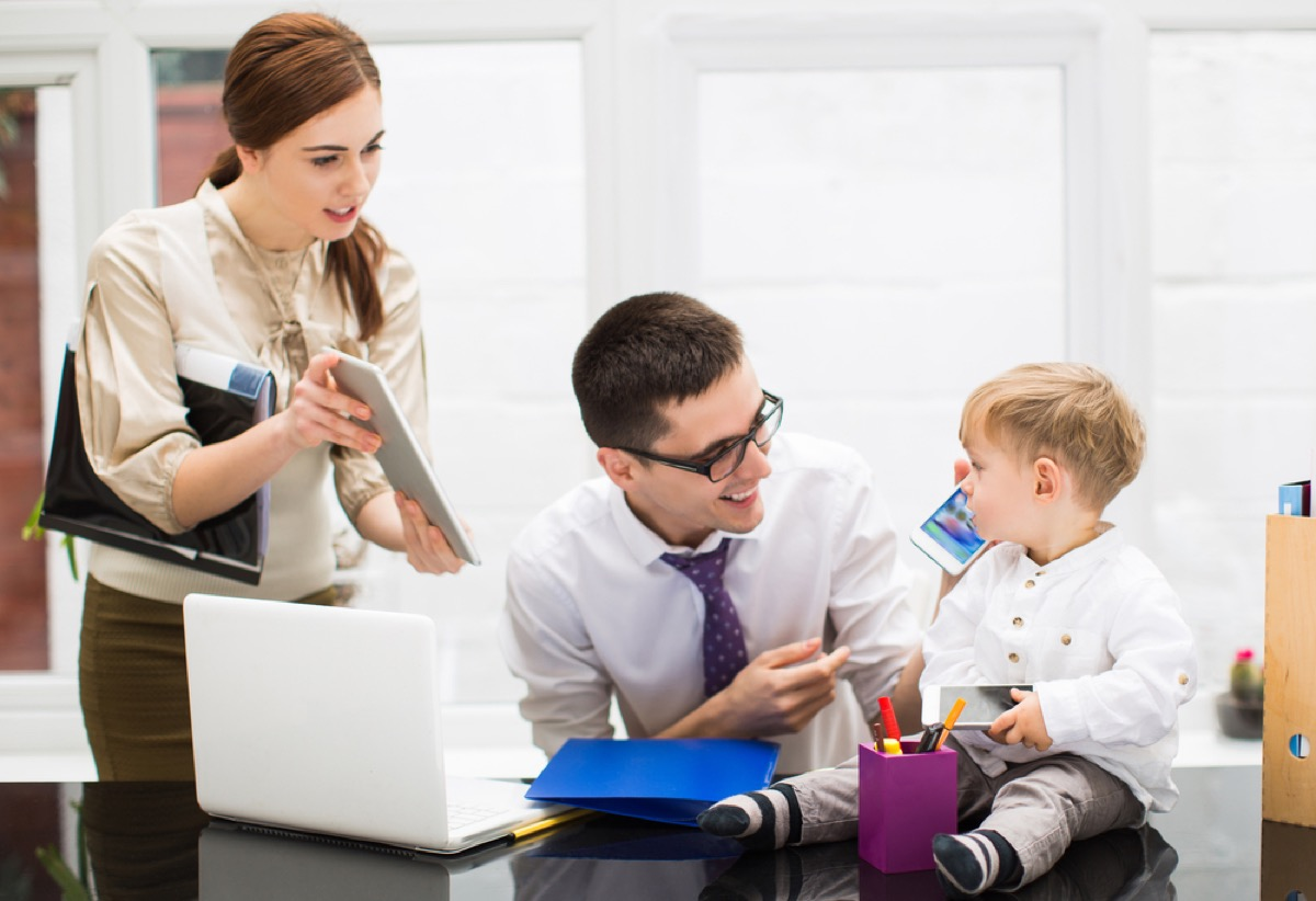 mom and dad working with baby, ways parenting has changed.