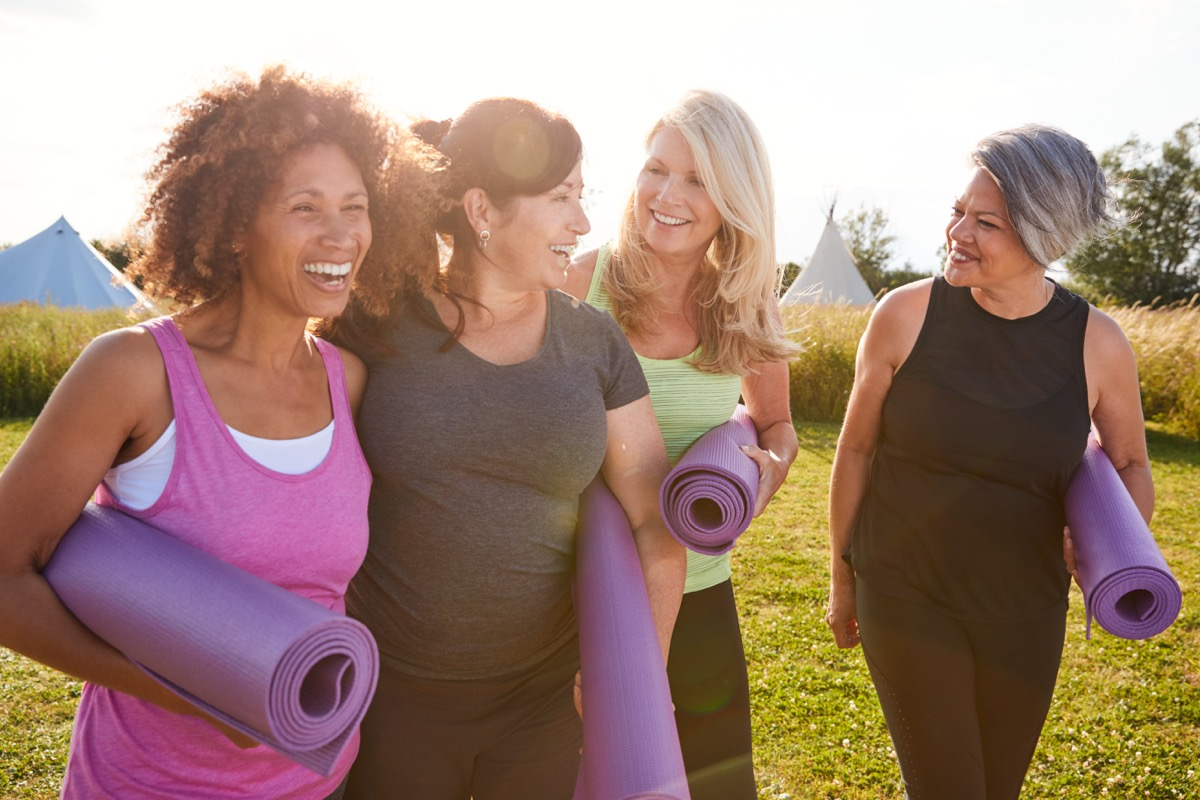 Older group of friends leaving yoga class with mats