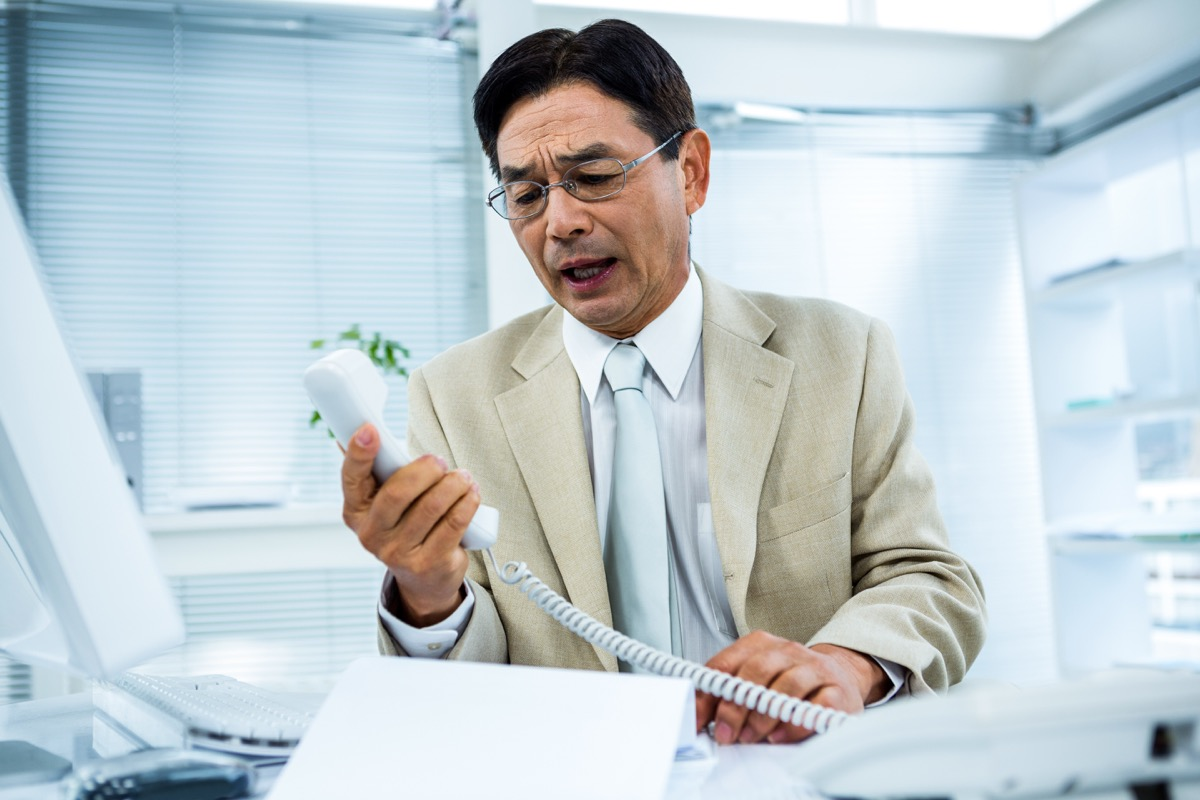 Angry Asian business man middleaged on phone, things not to say to customer service