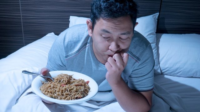 Man sits up in bed late at night with plate of noodles