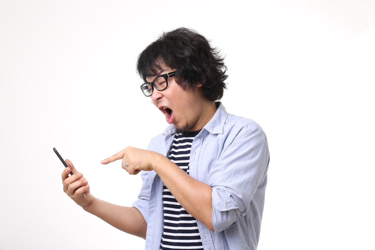 asian man with glasses and long hair screams and points at phone, hings not to say to customer service rep