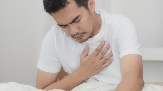 Asian Man Holding His Chest in Pain from Pneumonia Misdiagnosed Men's Health issues