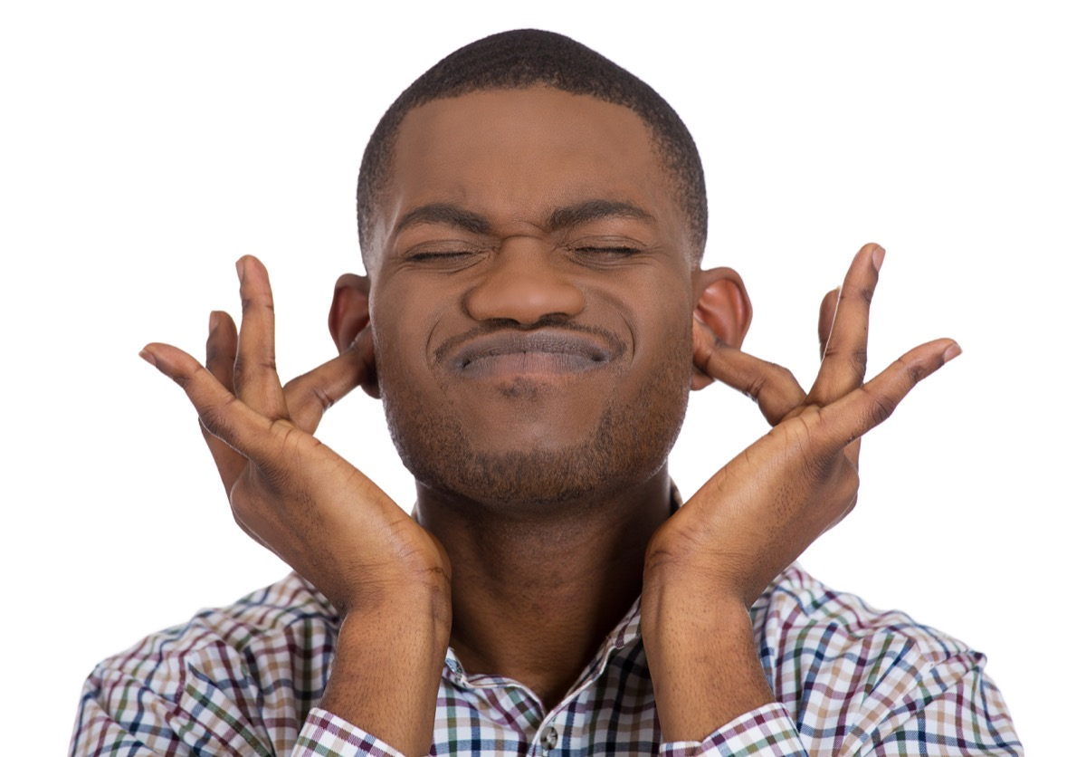 Black man puts fingers in his ears because he does not want to listen, check hearing to be a healthier man
