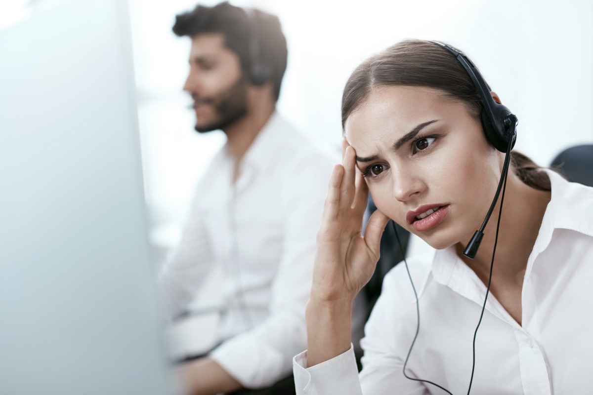 young female customer service rep looks annoyed while using headset, things never to say to customer service rep