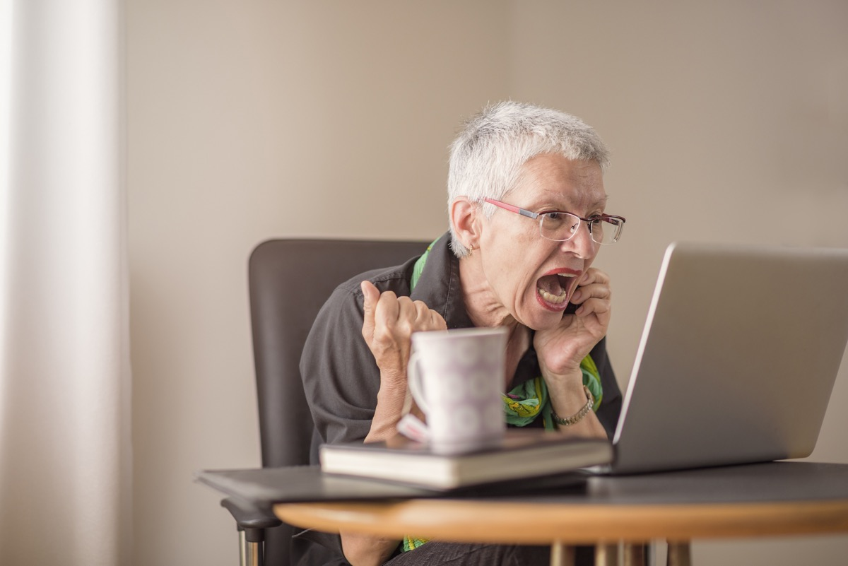 Elderly woman with white short hair and glasses screams at computer while on phone, things not to say to customer service rep