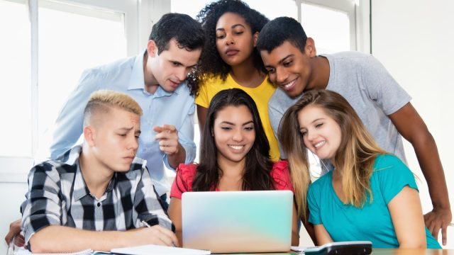 Multiracial students gather around computer, looking at memes for English Teacher Meme Project