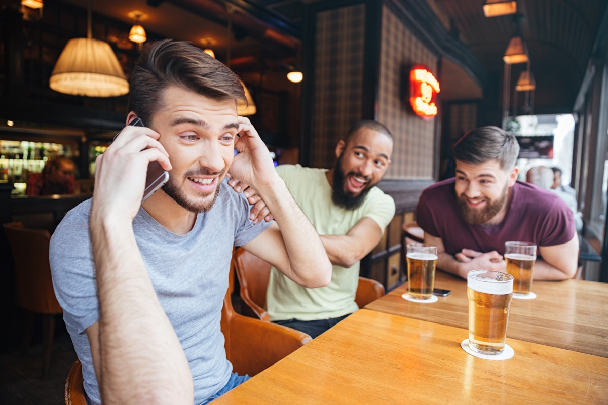 Man on phone in bar with friends drinking beer, things not to say to customer service