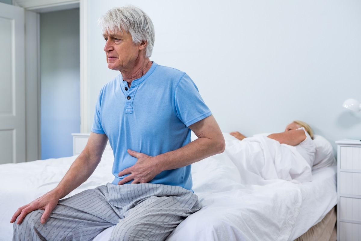 senior man with white hair sits at edge of bed holding stomach while wife sleeps, what your stomach pain could mean