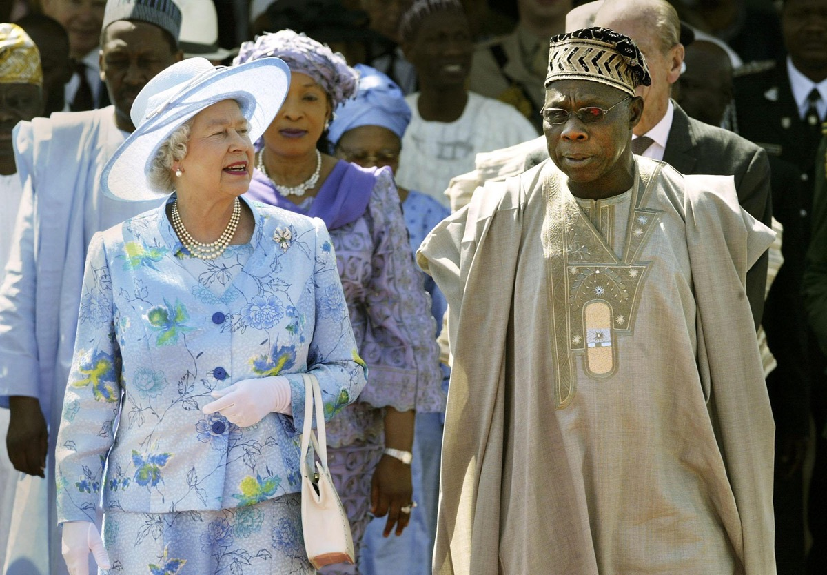 Queen Elizabeth II is escorted by Nigerian President Olusegun Obasanjo whom Prince Philip offended among controversial moments