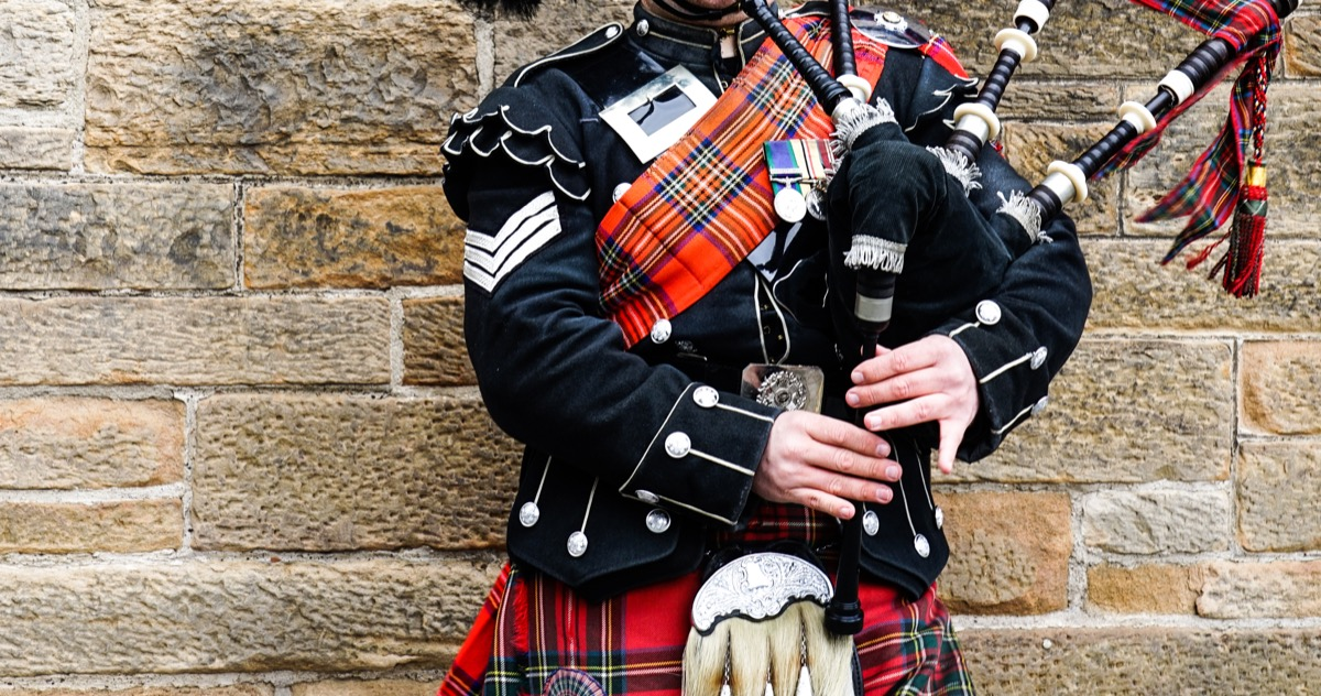 Scottish bagpiper dressed in traditional red and black tartan dress stand before stone wall, Prince Philip controversial moments
