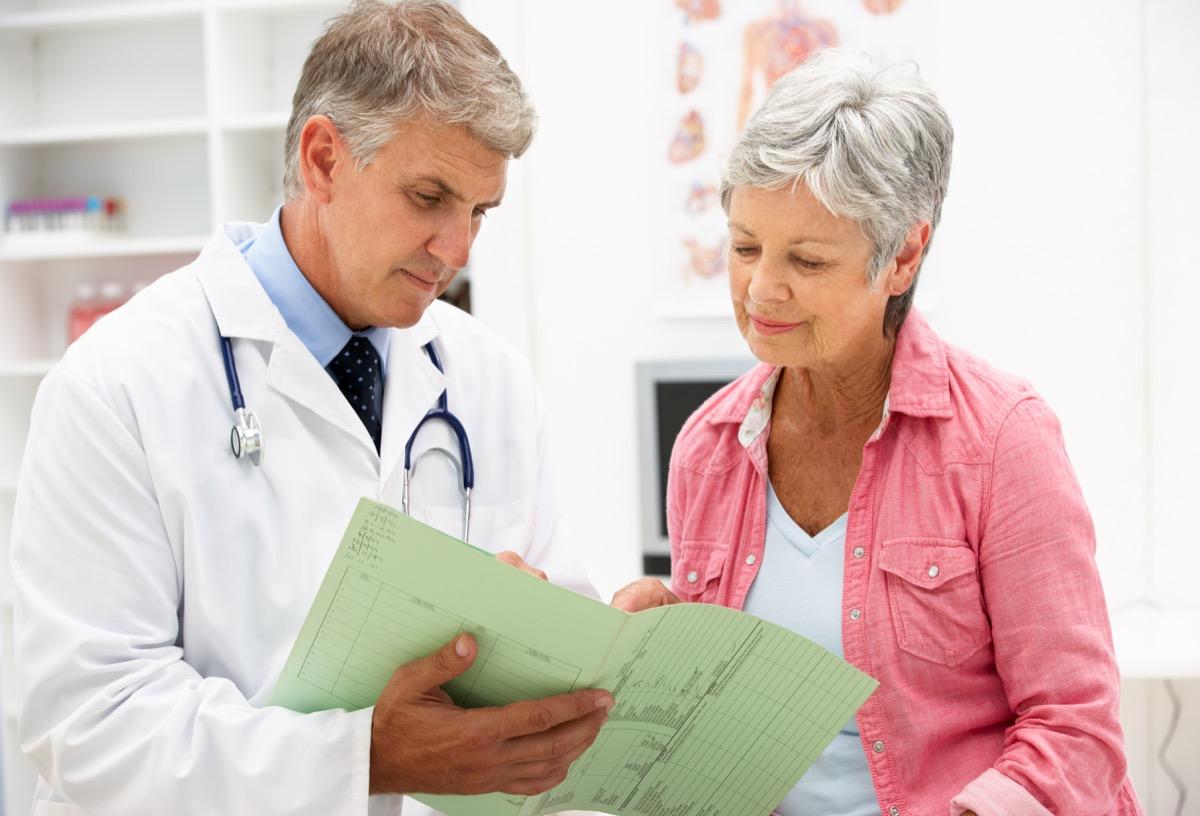 Senior woman with short gray hair talking to white male senior doctor, empty nest