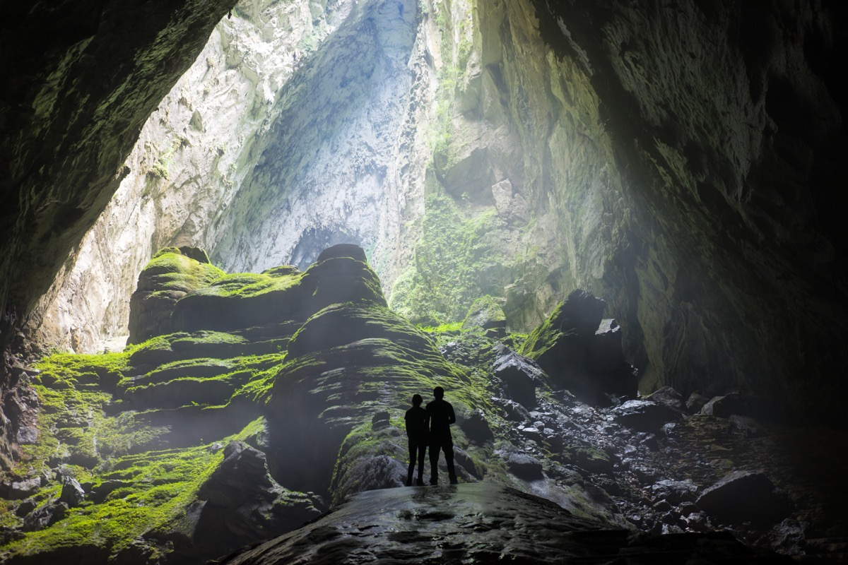 the backs of two people standing in a huge cave