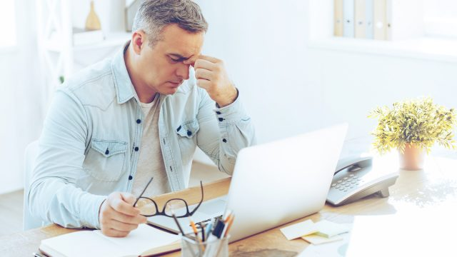 Tired man with gray hair sitting at desk