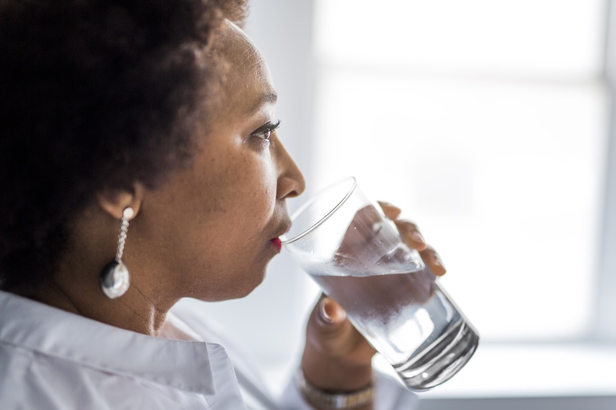 Black woman of middle age drinks water, heath for women over 40