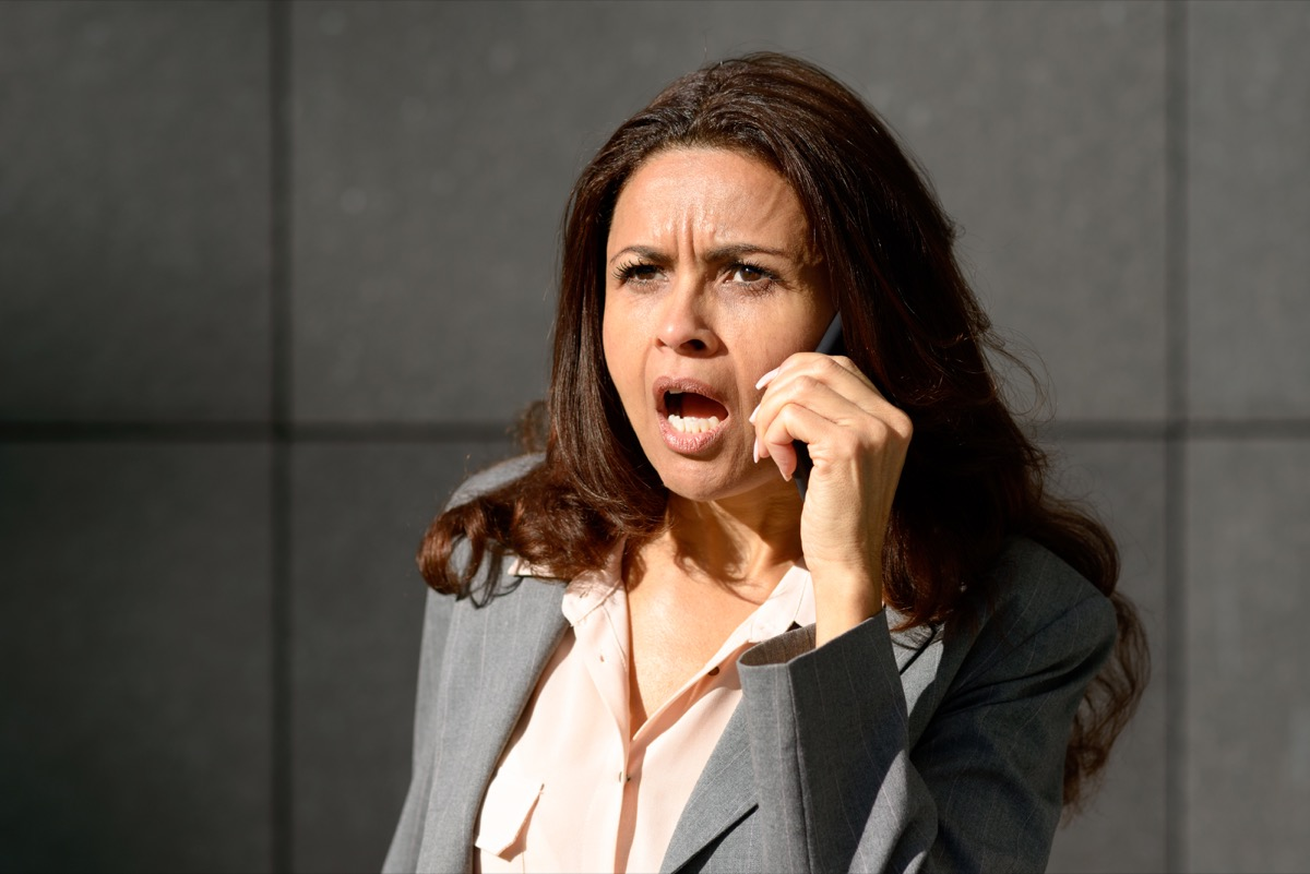businesswoman of color screams on phone wearing suit, things not to say to customer service rep