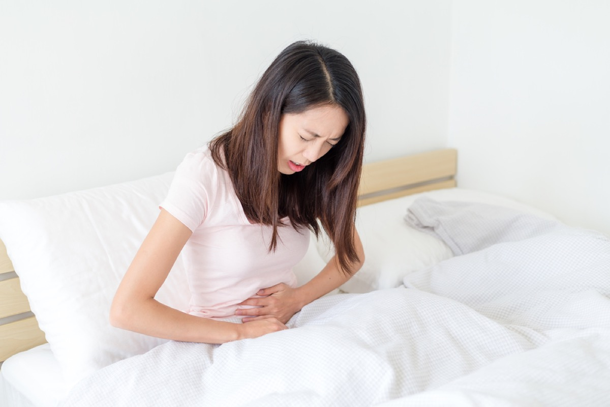 young woman with stomach pain curled over in bed, stomach symptoms
