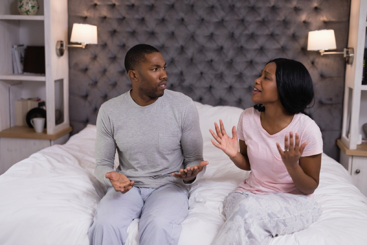Young couple sitting on bed having argument