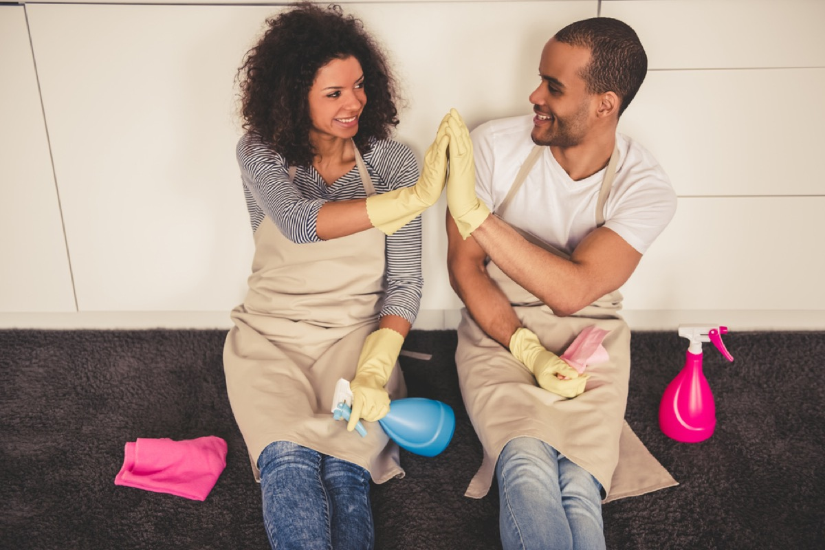 young black couple wearing cleaning gloves high fiving while sitting on kitchen floor with cleaning products