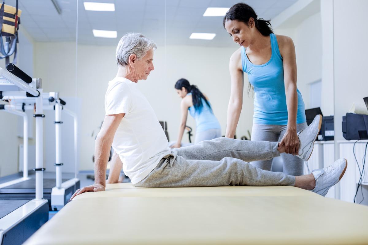 man's body feels weak so a woman is checking his leg