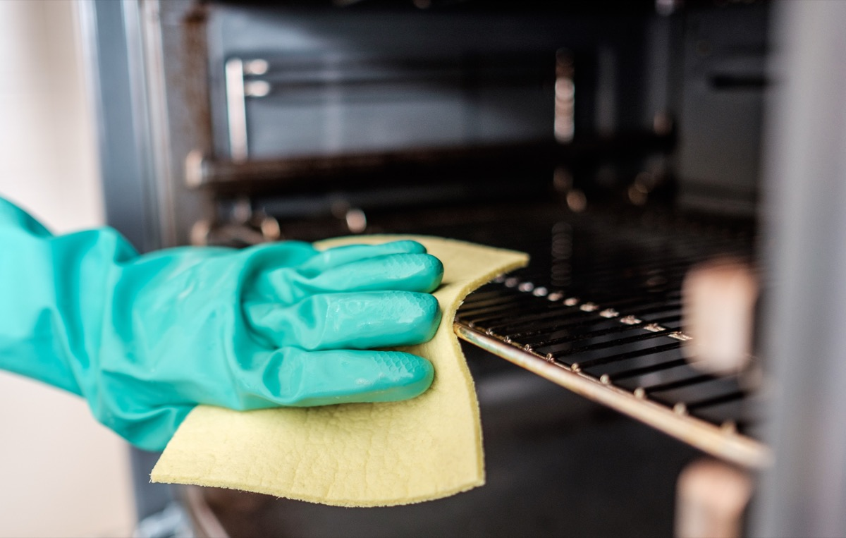 gloved hand cleaning oven