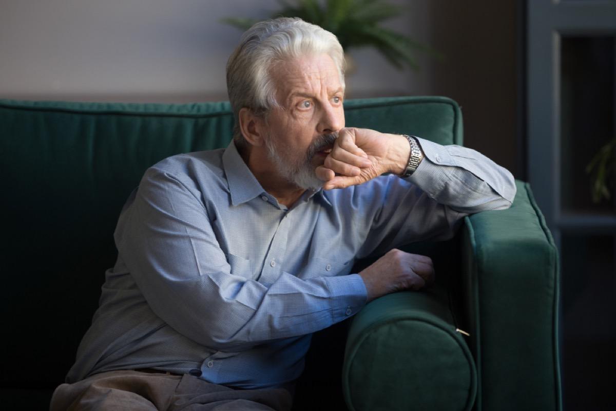 concerned older man sitting on couch