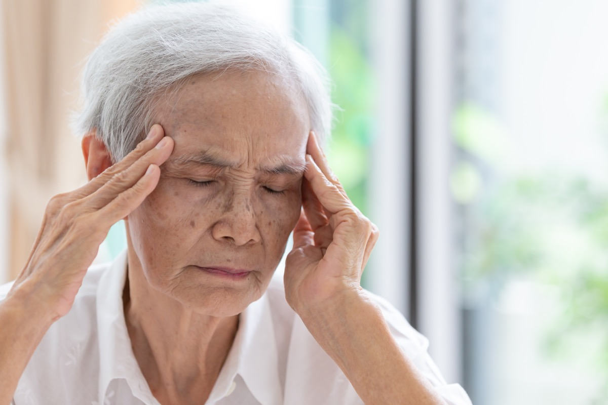 a woman with gray hair is experiencing a headache