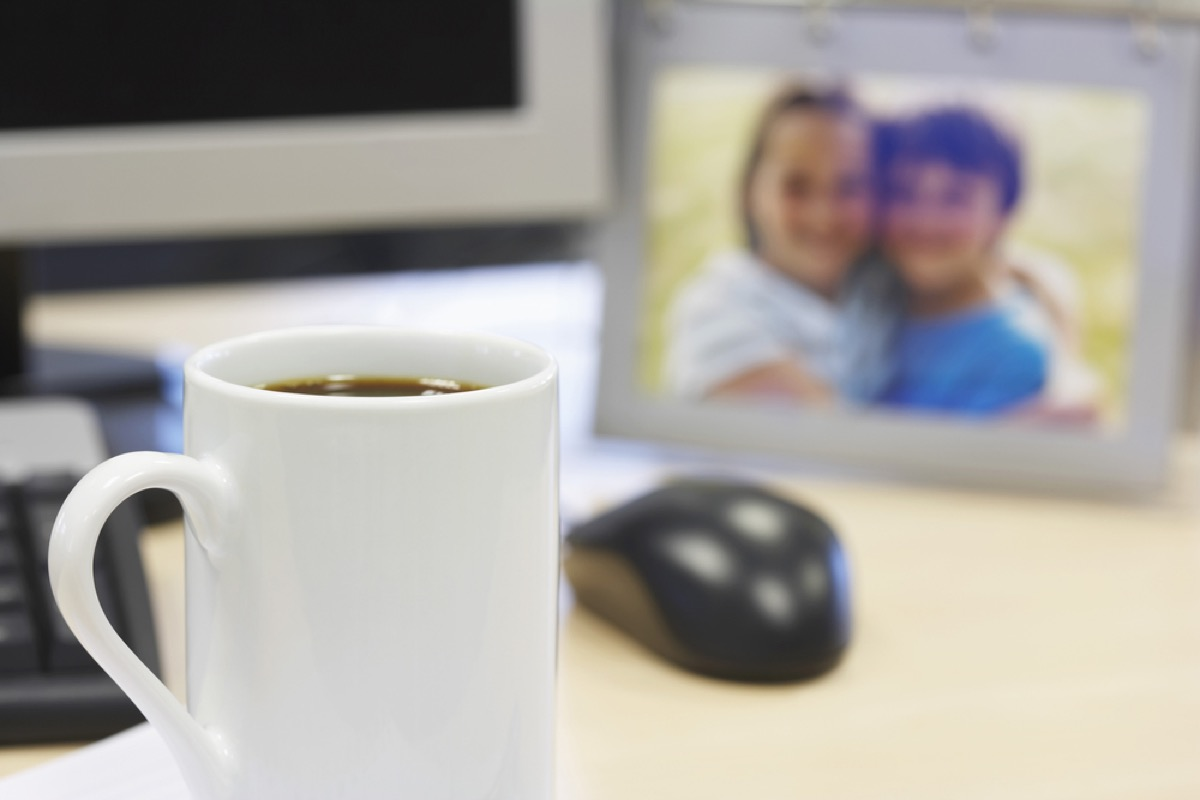 desk with mouse, coffee mug, and family photo, office etiquette