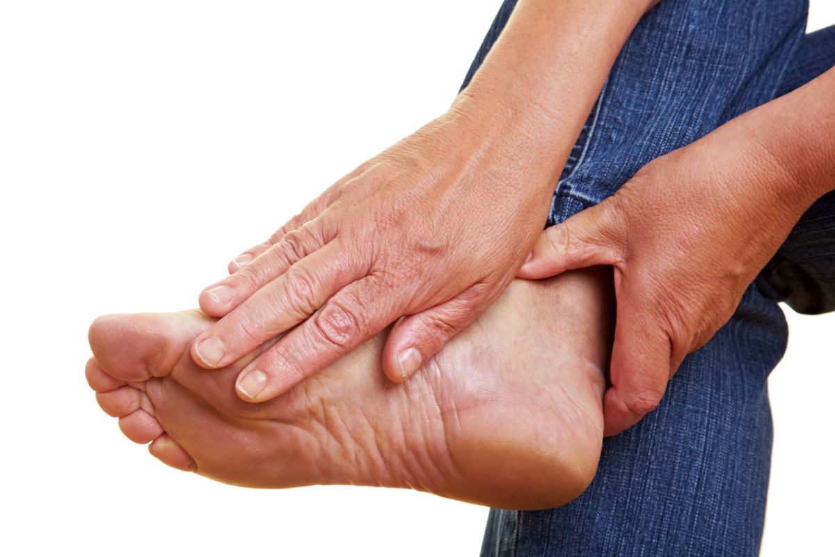 Woman Rubbing Her Foot in Pain Aching Feet