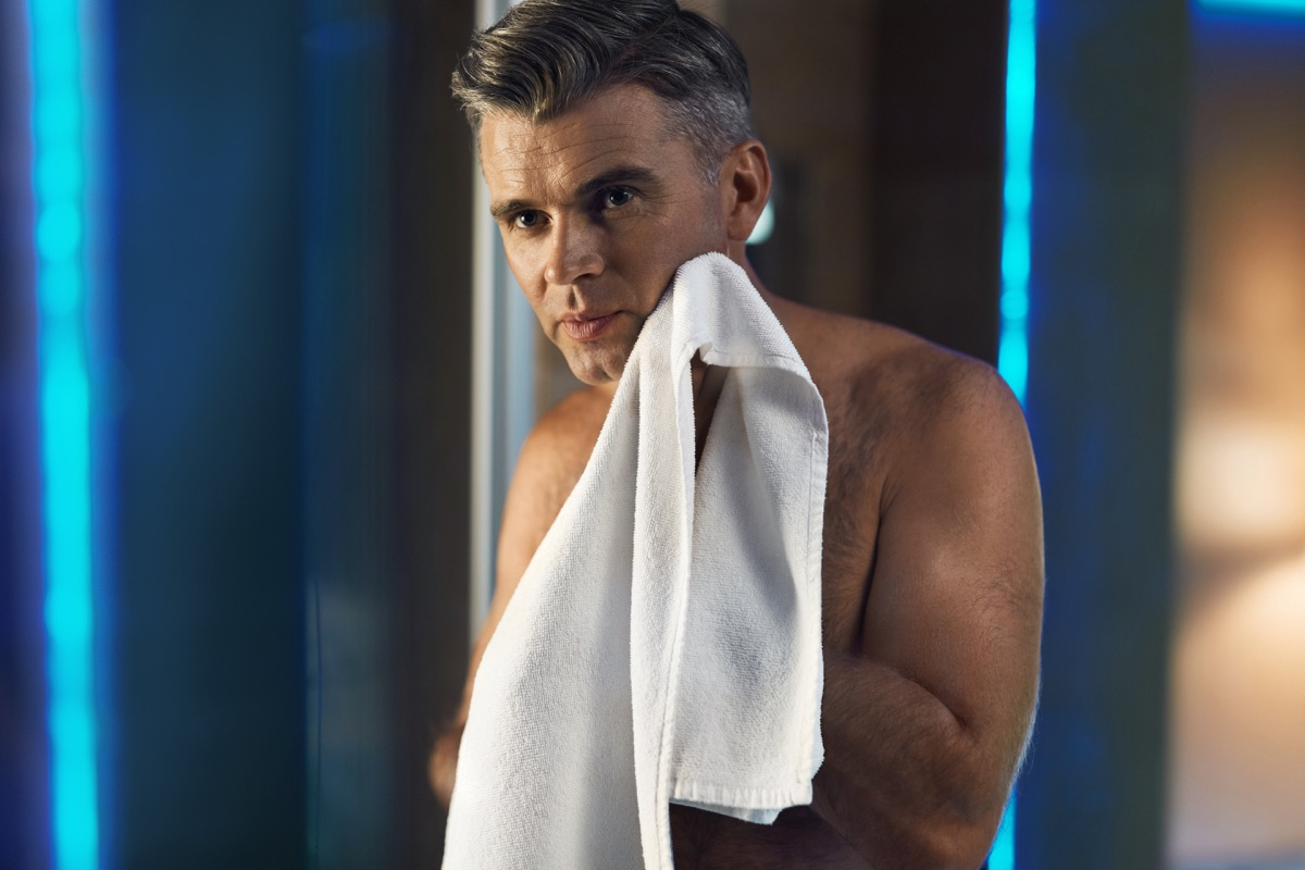 a man with gray hair holding a face towel