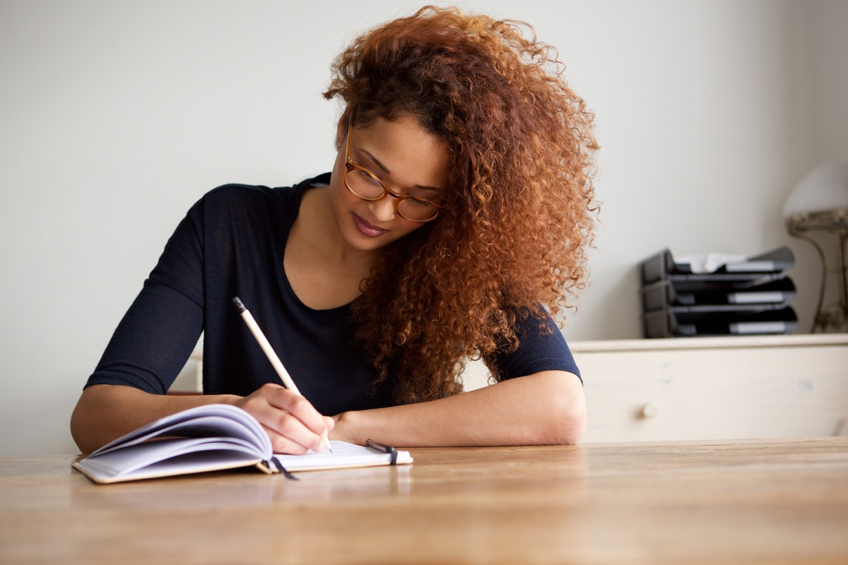 young woman writing in a notebook