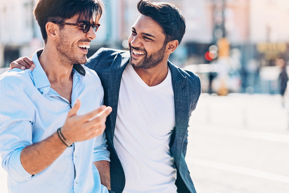 two young indian men laughing together on the street