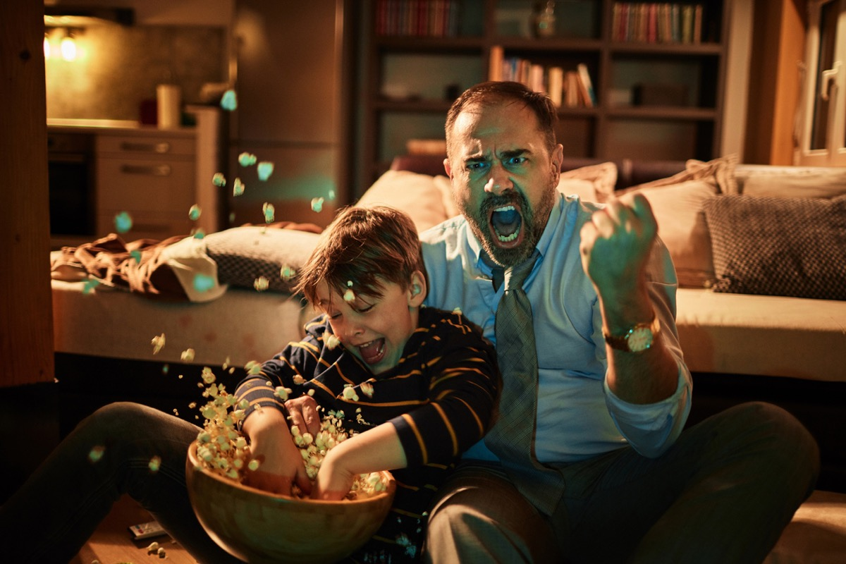man dressed up excited while watching TV with son throwing popcorn