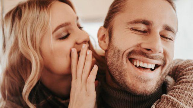 white woman whispering to laughing white man