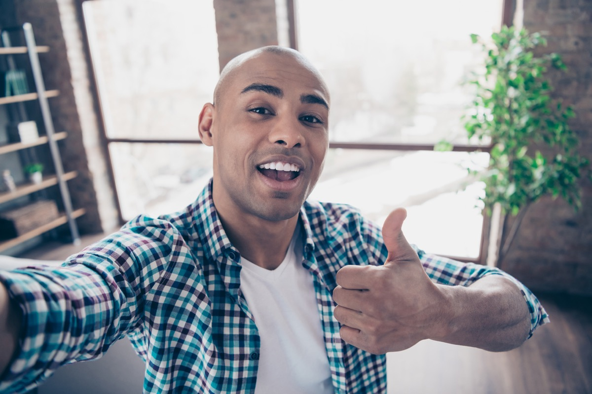 young black man taking a selfie and giving a thumbs up
